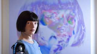 Ai-Da stands in front of one of 'her' artworks.