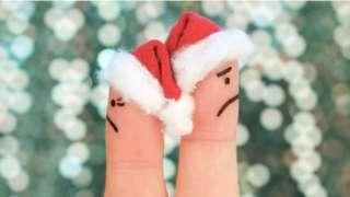 Dedos com rostos pintados e chapéu de papai noel de costas um para o outro