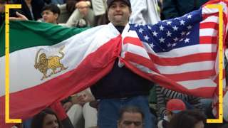 An Iran fan holds up the pre-revolution flag of Iran, and that of the USA