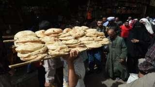 رجل يحمل فوق رأسه خبزا في شارع مزدحم