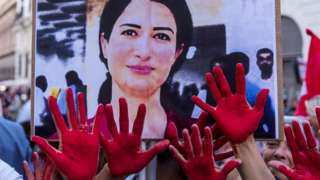 Protestors in Italy with hands marked red gather to remember Hevrin Khalaf