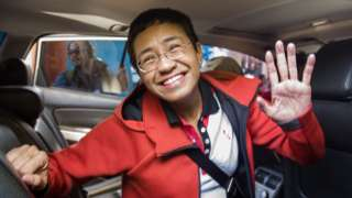 Philippine journalist Maria Ressa waves to photographers after posting bail outside a court building in Manila in March 2019
