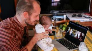 Namibian citizen Phillip Luhl holds one of his twin daughters as he speaks to his Mexican husband Guillermo Delgado via Zoom meeting in Johannesburg,