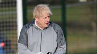 """British Prime Minister Boris Johnson puts on goalkeeping gloves before a girls"""" soccer match during an election campaign event on December 7, 2019 in Cheadle Hulme, United Kingdom"""