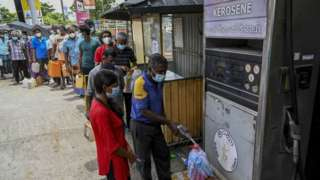 People stand in a queue to buy kerosene oil used in cooking stoves in Colombo on August 31, 2021 following Sri Lanka's declaration of state of emergency over food shortages as private banks ran out of foreign exchange to finance imports.