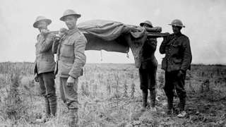 Allied forces carrying a dead soldier on a stretcher during the World War One Battle of the Somme