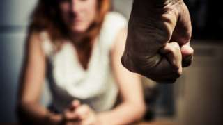 Man with clenched fist standing in front of woman (posed photo)