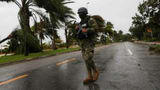 A soldier stands guard along an avenue Tulum after Hurricane Delta hit, in the state of Quintana Roo, in Cancun, Mexico October 7, 2020