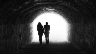 Silhouetted characters in tunnel