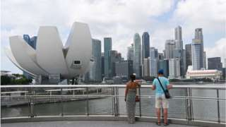 Tourists view the ArtScience Museum (L) in Marina Bay in Singapore.
