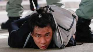 """A man lies on the ground as he is detained by riot police during a march against the national security law at the anniversary of Hong Kong""""s handover to China from Britain in Hong Kong, China July 1, 2020."""