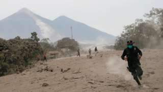 A police officer runs away from a new pyroclastic flow spewed by the Fuego volcano in the community of San Miguel Los Lotes in Escuintla, Guatemala, June 4, 2018