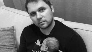 Christopher Jones holding his baby while sitting on a sofa.