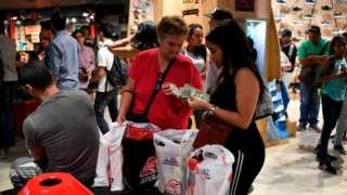 Em shopping, duas mulheres mexem com notas de dólares