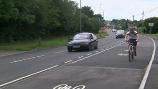 Cyclist travels along a cycle lane in Wimborne, Dorset