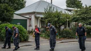A line of police officers search a road nearthe Al Noor mosque, site of one of the attacks, in Christchurch