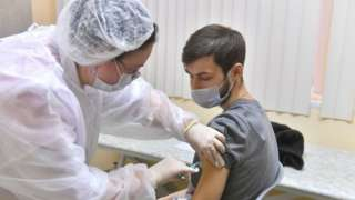Man receives vaccine at Moscow polyclinic - 5 December - Moscow News Agency handout photo