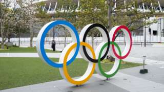 A man in a face mask stands behind a statue of the Olympic rings in Tokyo