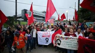Manifestantes pró-Lula em frente a prédio da Polícia Federal em Curitiba seguram cartazes e bandeiras