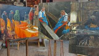 Three paintings by Henrietta Graham stand on easels in a studio