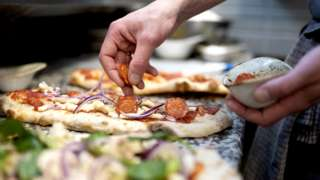 Stock image of someone putting toppings on a pizza