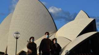 Pessoas usando máscaras na área externa da Sydney Opera House