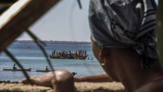 A woman watches as residents flee violence by boat