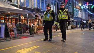 Two South Wales Police officers in uniform and helmets patrol bars area in Cardiff city centre after firebreak lockdown ends and venues reopened in November