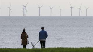 Couple with dog looking at wind farm