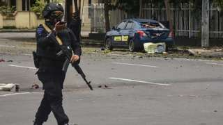 Indonesian police examine the site near a church after an explosion in Makassar