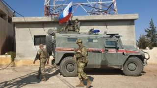 Russian soldiers walk past a Russian military police armoured vehicle at a position in the north-eastern Syrian city Kobane on 23 October 2019