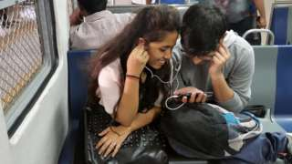 This photo taken on March 7, 2017 shows Indian students watching a movie on their smartphone while commuting on a suburban train in Mumbai. Buyouts, mergers and quick exits -- as India's richest man shakes up the country's ultra-competitive mobile market, telecommunications companies are scrambling to either consolidate or cut their losses and run.