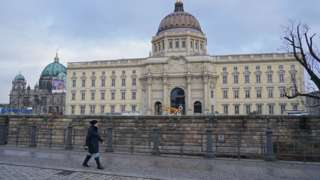 A woman walks past the Berlin Palace prior to the digitally streamed opening of the Humboldt Forum during the second wave of the coronavirus pandemic