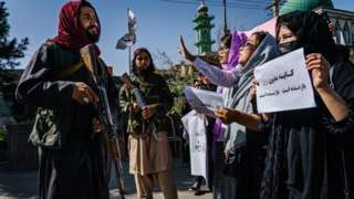 A Taliban fighter stares at demonstrators in Kabul