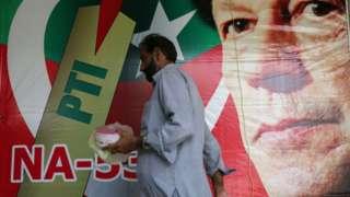 Man walks past poster of Imran Khan. 27 July 2018
