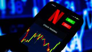 A stock trading graph of Netflix on a smartphone screen.