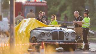 Police officers and Firefighters observe a Daimler wedding limo at the scene this morning as the sun comes up over the site. Hawker Hunter Plane Crashes During Display at Shoreham Airshow