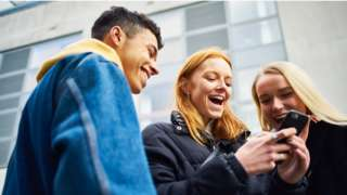 Group of people looking at a mobile