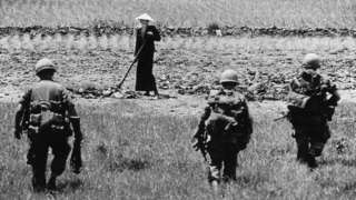 Soldiers approach an agricultural worker
