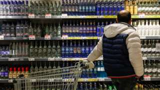 A man looks at a display of bottles of alcohol at a supermarket in Moscow.