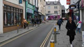 People walk past the shops on Stanley Street in Holyhead, Anglesey