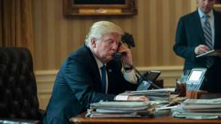 White House Chief of Staff Reince Priebus (R) looks on as President Donald Trump speaks on the phone with Russian President Vladimir Putin in the Oval Office of the White House, January 28, 2017 in Washington, DC
