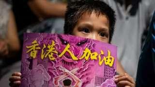 Một đứa trẻ giữ một tấm bảng trong cuộc biểu tình. Những người biểu tình chống chính phủ kỷ niệm 5 năm Phong trào Ô dù tại Công viên Tamar ở Hồng Kông.