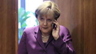 German Chancellor Angela Merkel uses her mobile phone before a meeting at a European Union summit in Brussels, 9 December 2011
