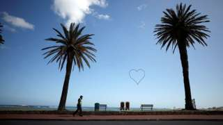 A security guard walks under palms at a deserted Camps Bay beach, South Africa