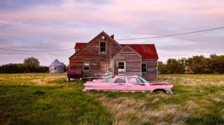 An abandoned pink car in front of a wooden house