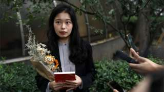 Zhou Xiaoxuan, also known by her online name Xianzi, speaks to supporters as she arrives at a court for a sexual harassment case involving a Chinese state TV host, in Beijing, China on 14 September 2021