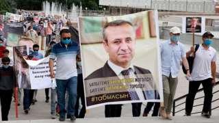 Протестующие с плакатом с изображением Орхана Инанды