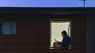 Girl wearing a face mask seen through a window - stock