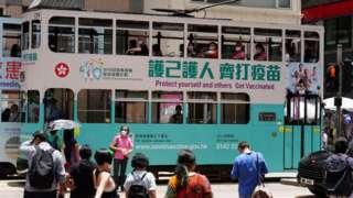 """一辆印有""""护己护人齐打疫苗""""车身广告的电车驶过香港湾仔街头(中新社图片19/5/2021)"""